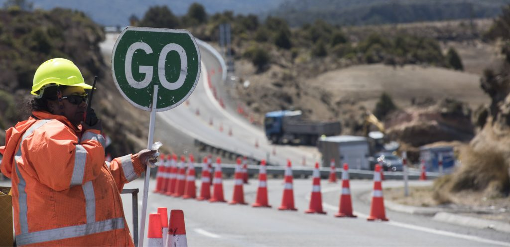 """Construction worker holds up a """"go"""" sign at roadworks"""
