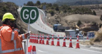 "Construction worker holds up a ""go"" sign at roadworks"